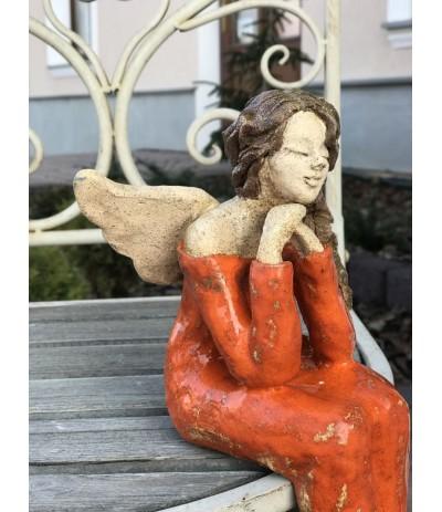 Bog.Kącik Anioł ceramiczny siedzący pomarańcz